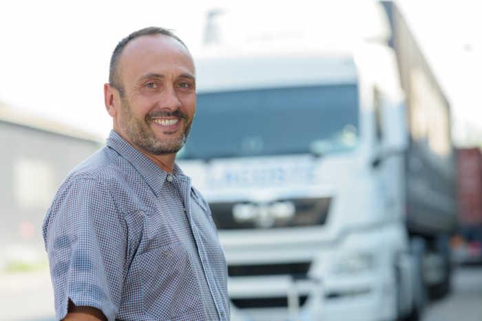 Ein Spediteur steht vor seinem Lastwagen und lächelt